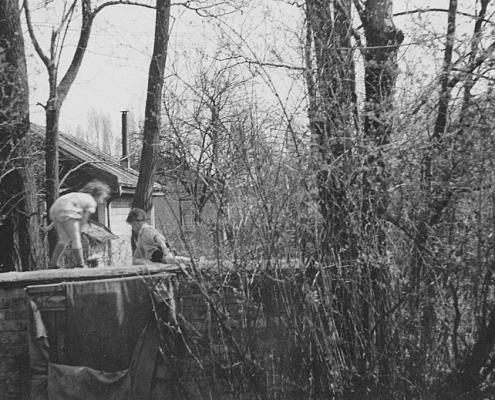 Renate und Manfred Richter spielen auf dem alten Bierkeller, Richtung südlicher Angelverein. Der Bierkeller entstand vermutlich in den 30er oder 40er Jahren, war gemauert und befand sich halb unter der Erde. Im Sommer wurde hier das Bier vorgekühlt. Er hatte ein mit Dachpappe gedecktes Schrägdach. Nachdem 1952 die heutige Küche mit Schankanlage und neuem Keller im Zuge der Errichtung der massiven Clubkantine fertiggestellt war, wurde der alte Bierkeller noch als Motorbunker verwendet. Er wurde während der Planung des Garderobenneubaus abgerissen. Die Bootsmotoren wurden danach in den heutigen Betonkästen untergebracht.